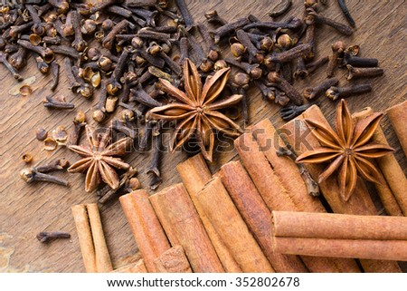 cinnamon sticks, star anise and cloves on wooden background - stock photo