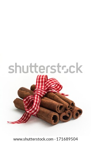 cinnamon sticks with checked Christmas bow. Can be used as a background for Christmas card. /  Cinnamon sticks - stock photo
