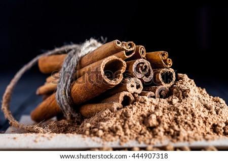 Cinnamon sticks with cinamon powder linked with twine. Black background. Macro image - stock photo