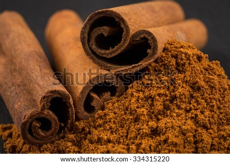 Cinnamon sticks with cinnamon powder on stone plate background