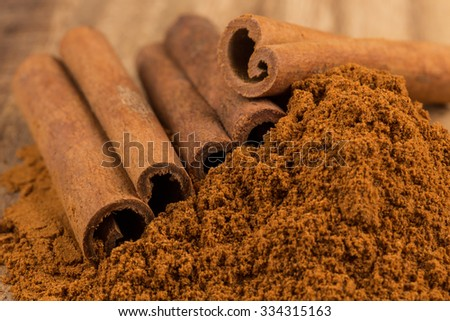Cinnamon sticks with cinnamon powder on wooden background