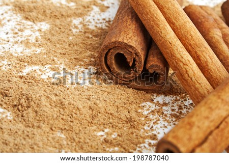 Cinnamon sticks with its dust around it over a white background - stock photo