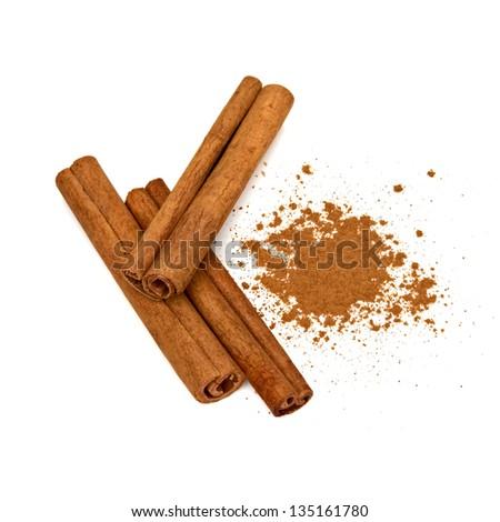 Cinnamon sticks with powder pile on white background - stock photo