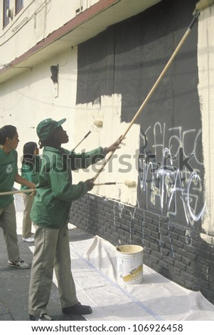 CIRCA 1990 - A group of kids repainting the side of a building defaced by graffiti - stock photo