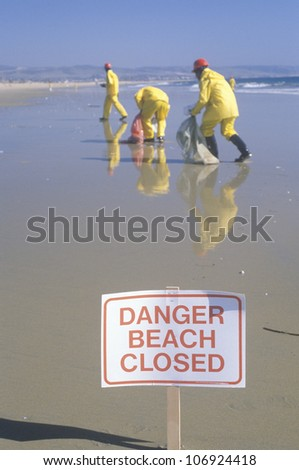 "CIRCA 1990 - A sign warning ""Danger"" after an oil spill closed Huntington Beach, as cleanup workers remove oil from the California shoreline - stock photo"