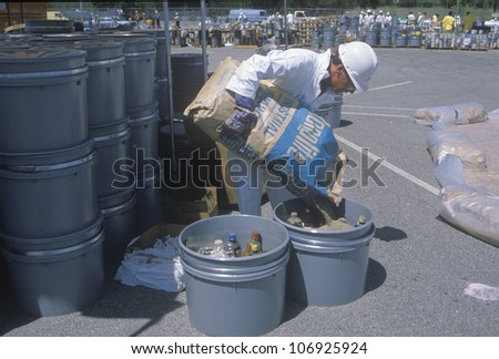 CIRCA 1990 - A worker pouring the contents of a bag into a container of waste materials at waste cleanup site on Earth Day at the Unocal plant in Wilmington, Los Angeles, CA - stock photo