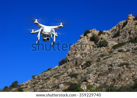 Circa, Circa - January 6, 2016: White drone equipped with high resolution 4K video camera hovering in mid air with a blurred cliff in the background