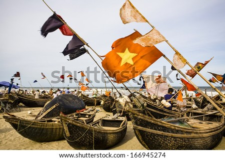CIRCA JULY 2011 - THANH HOA, VIETNAM - Flags fly from fishing boats on Sam Son Beach, on 1 July 2011, in Thanh Hoa, Vietnam