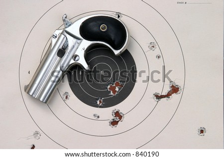 Circa 1889, Model 95, Type II Model 3 Double Derringer, a paper target with bullet holes in it - stock photo