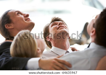 Circle of business people embracing each other while looking upwards - stock photo