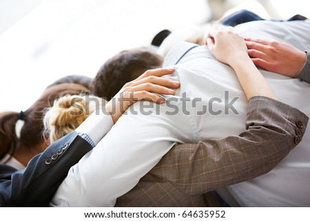 Circle of business people embracing each other with their heads bowed while concentrating