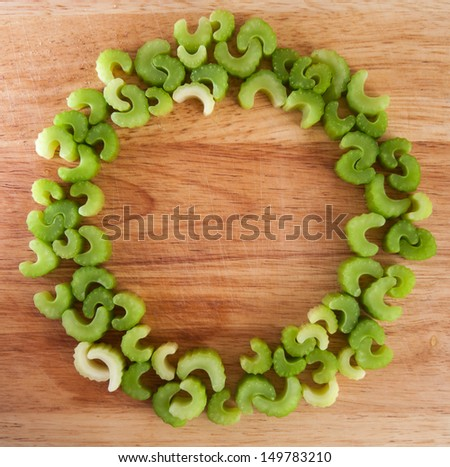 Circle of chopped celery on wood chopping board background - stock photo