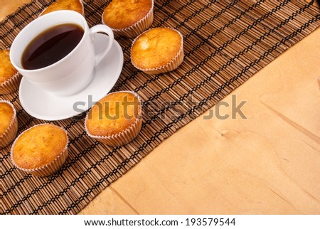 Circle of cupcakes around cup of coffee on wooden mat. - stock photo