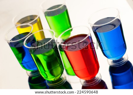 Circle of multicolored alcohol drinks in shot glasses