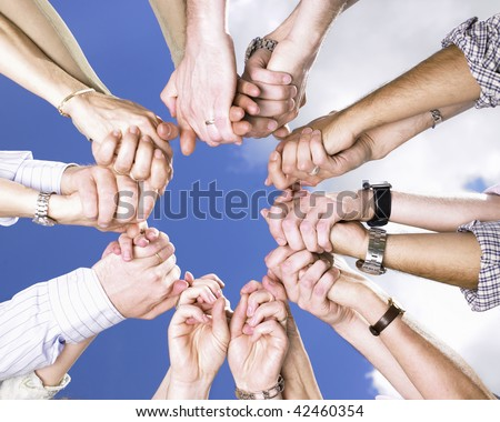 Circle of people's arms, holding hands, with blue sky and clouds in the background. Square. - stock photo