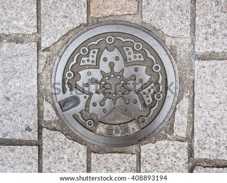 Circle steel manhole cover on polished stone sidewalk in Japan - stock photo