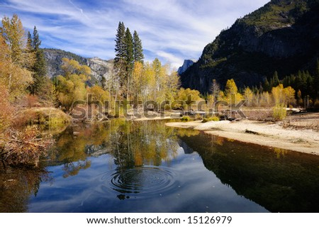 Circles are spreading on a smooth surface of Merced river with beautiful autumn colors contrasting with gray granite walls of Yosemite valley. - stock photo