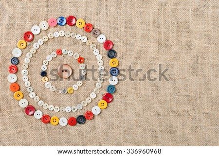 Circles of colorful sewing buttons on fabric texture background with copy space - stock photo