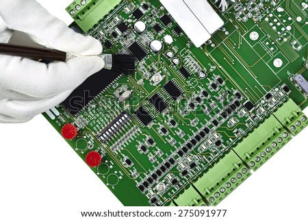 Circuit board with hand in white glove holding brush cleaning the board isolated on white