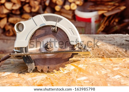 Circular electric saw on the desktop with the wood. - stock photo