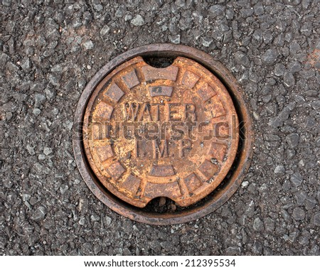 Circular manhole cover for water drain in pavement. - stock photo