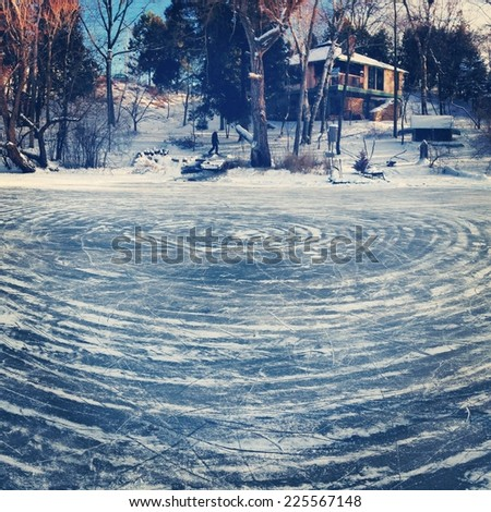 Circular patterns in the ice of a frozen lake with a house on a nearby hillside. - stock photo