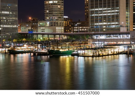 Circular Quay railway, train station and ferry wharfs with Sydney Central Business District, downtown  skyscrapers at the background. Cityscape night shot, long exposure, copy space - stock photo