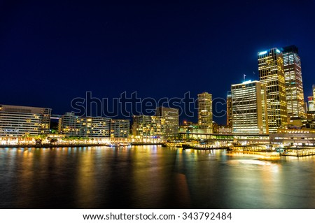 Circular Quay,  Sydney Business District Centre, train and ferry station at night, with illuminated skyscrapers and ferries. Sydney, Australia. Long exposure - stock photo