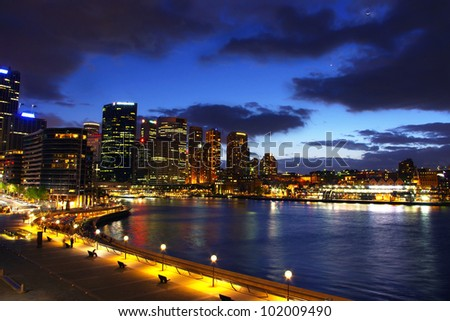 circular quay with sydney city skyline at night with clouds and lights - stock photo