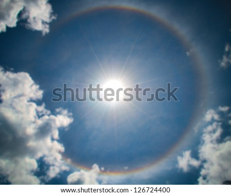 Circular Rainbow Around Sun with clouds - stock photo
