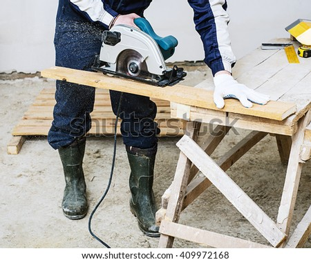 circular saw for cutting boards into the hands of the builder, the man sawed bars, construction and home renovation, repair and construction tool
