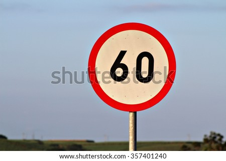 Circular speed limit road sign with the number sixty on it on the side of the road.