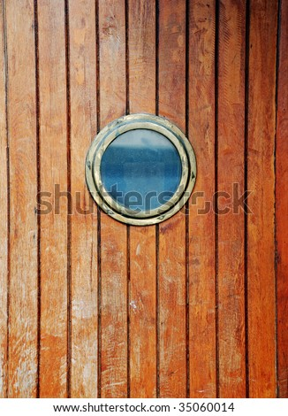 circular window on a timber door of a boat - stock photo