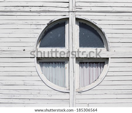 Circular window on wooden house - stock photo