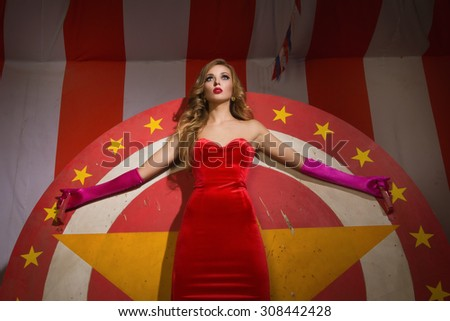 Circus actress in a red dress stands on circular disc with star