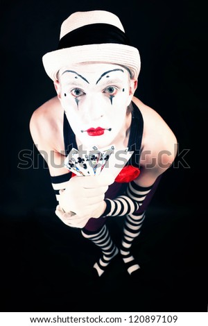 Circus clown in makeup with playing cards on a black background