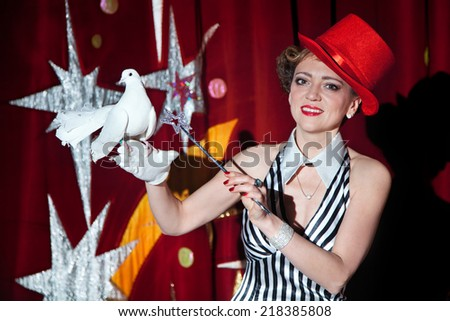 Circus magician artist woman posing with a white dove on her hand in glow of spotlight