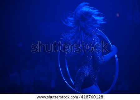 Circus performance concept. Dancing woman rotates hula hoop in show watchers background. Blue circus illumination. Copy-space. Indoor shot