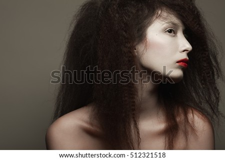 Circus performer concept. Emotive portrait of fashionable model with long curly hair and artistic make-up posing over grey background. Perfect skin. Retro style. Copy-space. Close up. Studio shot