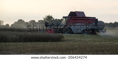 Cirencester, Gloucestershire, July 17th 2014 - Massey Ferguson Combine Harvester working the field at night