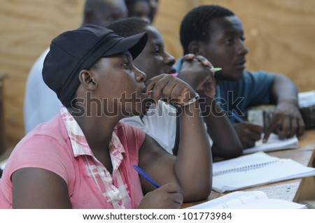CITE SOLEIL-AUGUST 25: Mature students attending classes in a local community school in Cite Soleil- one of the poorest area in the Western Hemisphere on August 25 2010 in Cite Soleil, Haiti. - stock photo