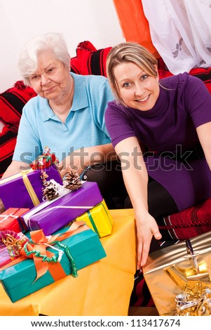 citizen senior and young woman with many presents