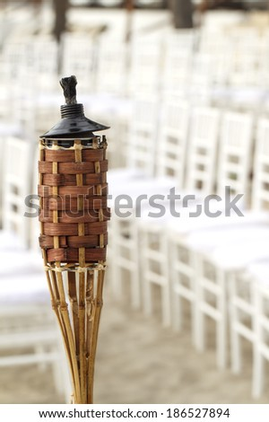 Citronella torch on beach - stock photo