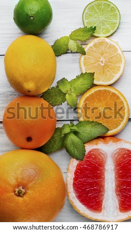 Citrus and mint on white wooden background. Lime, lemon, grapefruits, orange whole and ripe. Closeup