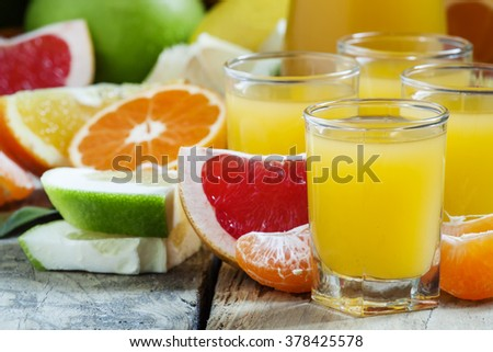 Citrus cocktail, jug, pieces of fruit on a dark background, selective focus - stock photo