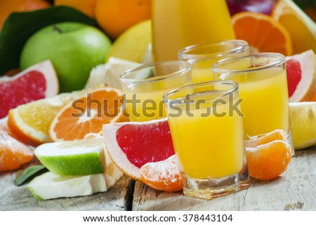 Citrus cocktail, jug, pieces of fruit on a dark background, selective focus
