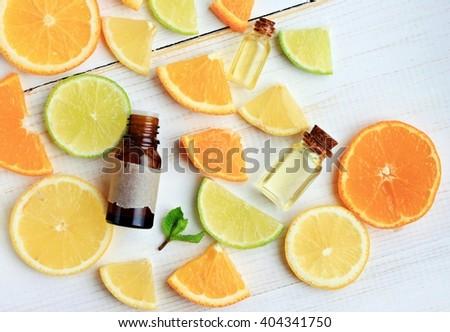 Citrus essential oil. Various citrus fruit and aroma bottles. Orange, lime, lemon slices. Top view. - stock photo