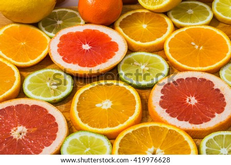 Citrus fruit background with sliced f oranges lemons lime tangerines and grapefruit as a symbol of healthy eating and immune system boost with natural vitamins. - stock photo