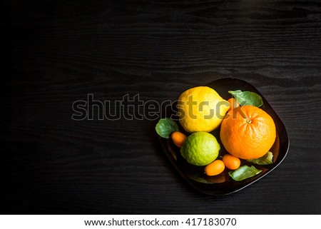 citrus fruit on black background, top view, flat lay - stock photo