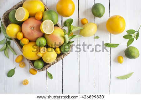 Citrus fruits family in basket on rustic white wooden background. Overhead view. Text space image. - stock photo
